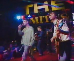The Smiths in 1984 (left to right): Morrissey, Andy Rourke, Johnny Marr, Mike Joyce (off-camera) (screen cap; YouTube)