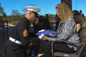A Marine Staff Sergeant presents the American flag to the daughter of the deceased during a funeral at the Miramar National Cemetery, San Diego. (U.S. Marine Corps photo by Lance Cpl. Harley Robinson/Released)